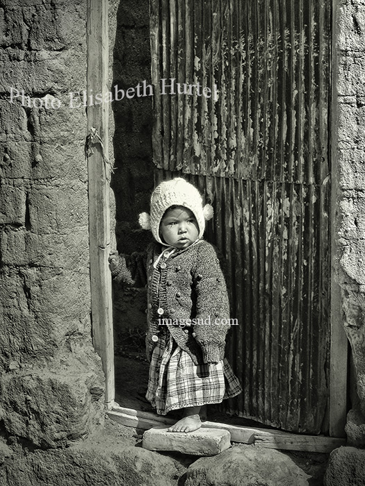 Kid on his doorstep, Bolivia altiplano village, street scene black and white