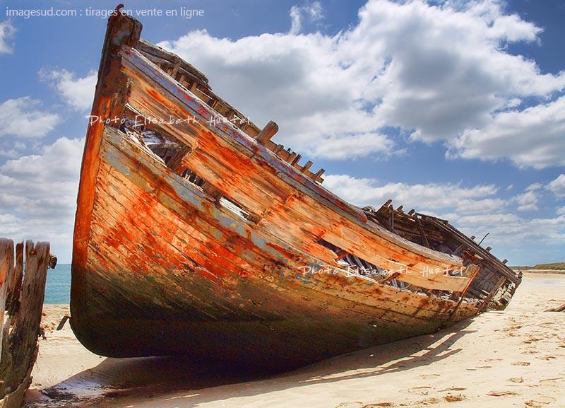 Photo d'une coque de bateau traditionnel échouée sur une plage, tirage d'art pour déco murale en vente en ligne.