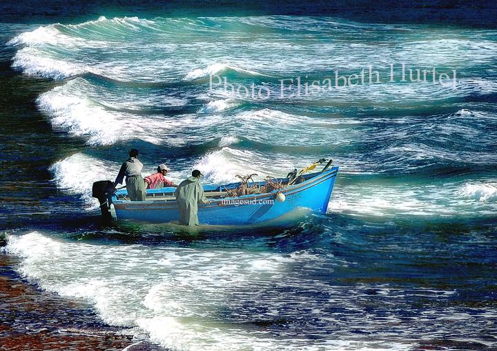 Barque de pêche, embarquement pour le large dans les déferlantes de la houle atlantique, scène de mer, photo d'art pour décoration