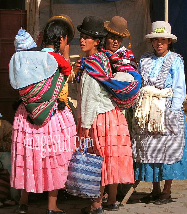 Jeunes cholitas Aymara en costume traditionnel, avec chapeau melon, pollera ou longue jupe sur les 7 jupons, et les bébés dans l'awayo sur le dos