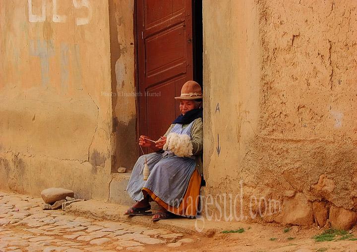 Bolivie : femme filant la laine sur le pas de sa porte, Tarata, valle alto