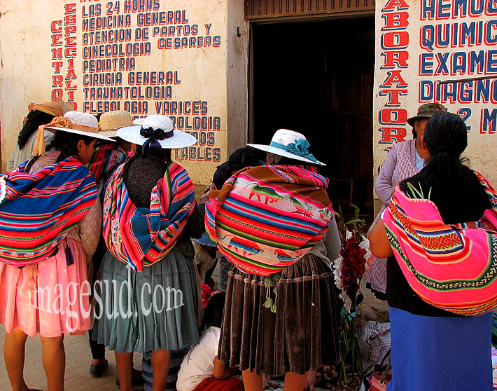 Bolivie : groupe d'indiennes en habits traditionnels, devant un dispensaire, scène de rue